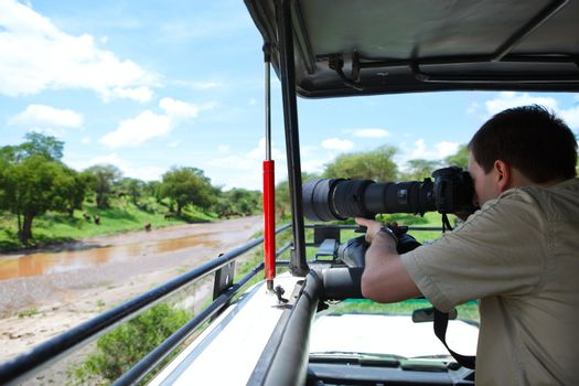 Safari vacation. Professional photographer taking picture on game drive in Tarangire national park, Tanzania. Elephants on packground.
