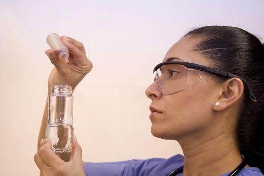 Pretty Hispanic nurse isolated on white testing chemicals