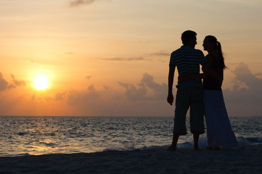 Silhouette of romantic couple on tropical beach at sunset