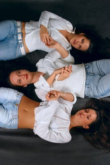 Three young girls lay on a floor in studio