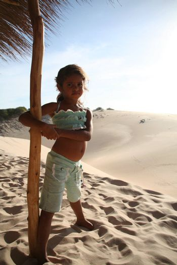 Young girl posing in the dunes of Cumbuco, state of Ceara, Brazil.