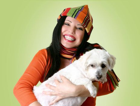 Smiling woman holding a small dog in her arms.