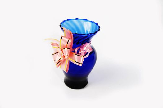 Blue vase with ribbon on white