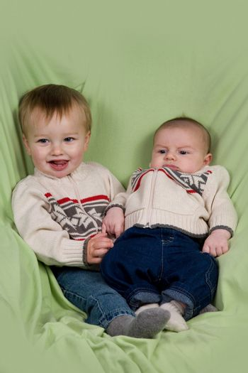 A portrait of two baby boys (cousins) in winter clothes.