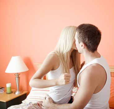 Young couple wearing white tank tops kiss passionately on the bed. Horizontal shot.