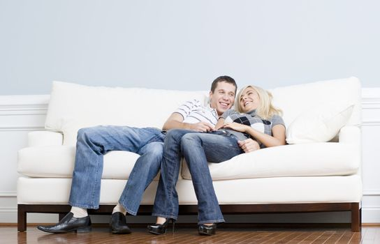 Full length view of affectionate couple laughing and relaxing together on white couch. Horizontal format.