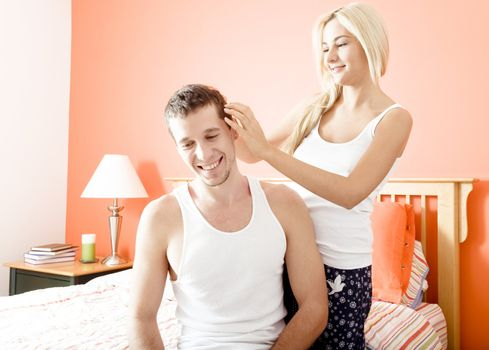 Woman ruffles man's hair as they relax in their bedroom. Horizontal format.