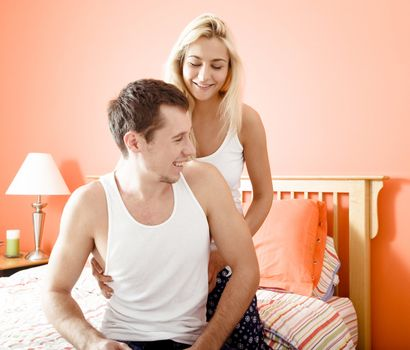 Affectionate couple in pajamas, smiling and relaxing in their bedroom. Horizontal format.