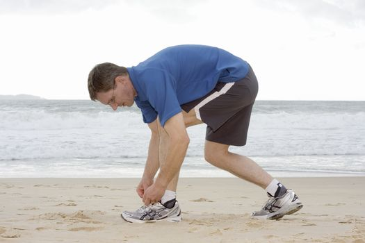 Runner tyine his shoes on a beach