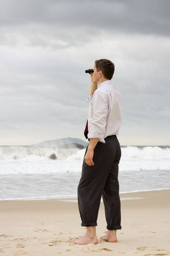 Businessman standing on a beach and searching with binoculars