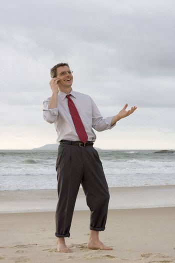 Businessman talking on cell phone while smiling and gesturing on a beach