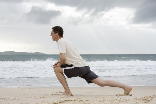 Mature man doing fitness exercises on a beach