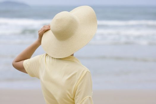 Woman with yellow hat and shirt looking at the sea - focus on the hat
