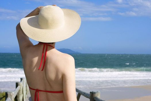 Woman with hat looking at the sea on a sunny day