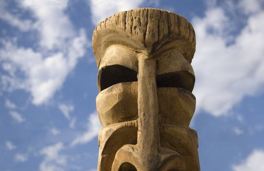 Hand-carved wooden tiki god against a bright summer sky