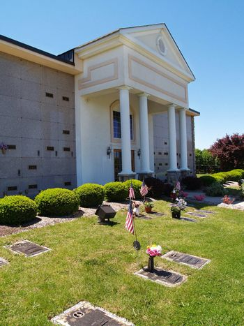 exterior of a mausoleum with flowers by graves