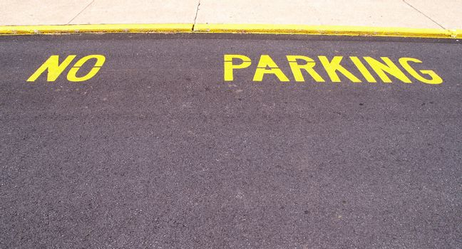 the words no parking painted on pavement