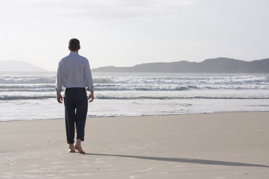 Lonesome businessman walking barefoot on a beach