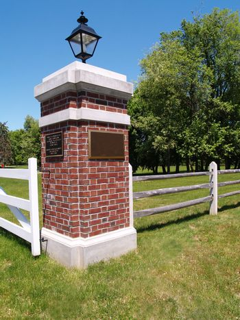 a brick lamp post by a wood fence in the country