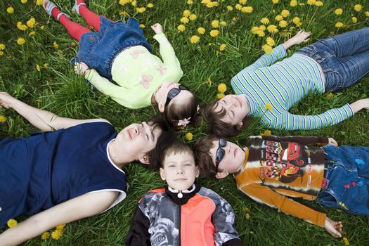 Children wearing sunglasses resting on the grass