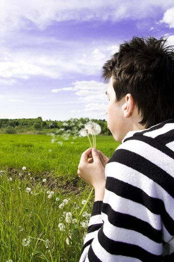 Young teenager blowing dandelion