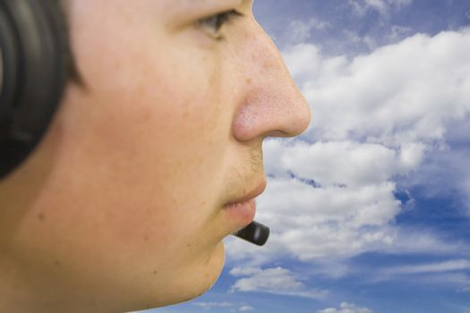 Travel-agency manager with headphones against blue and cloudy sky. Focus to mouth