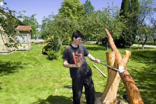 Young man in a garden does a balance swing