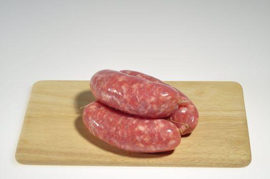 three fresh sausages on a cutting board