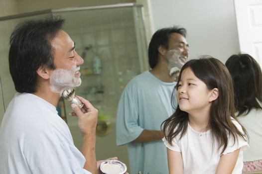 Man Shaving While Daughter Watches