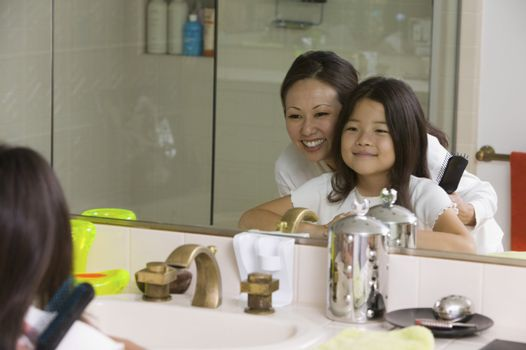 Mother and Daughter Looking in Bathroom Reflection