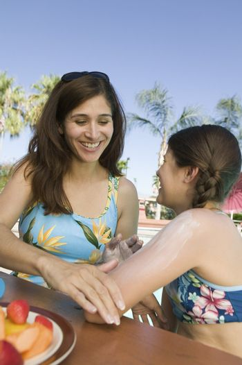Mother Rubbing Sunscreen on Daughter