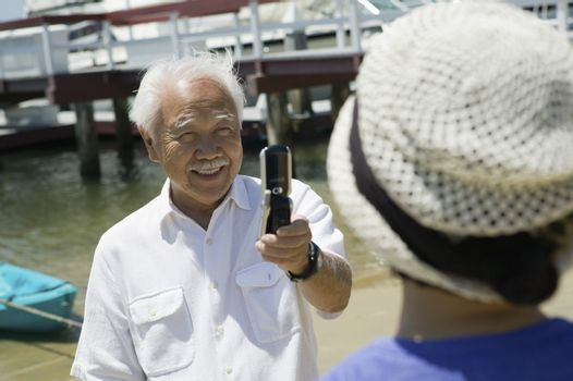 Man Taking Woman's Photograph with Camera Phone