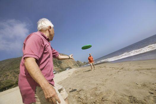 Two Men Throwing Frisbee on Beach