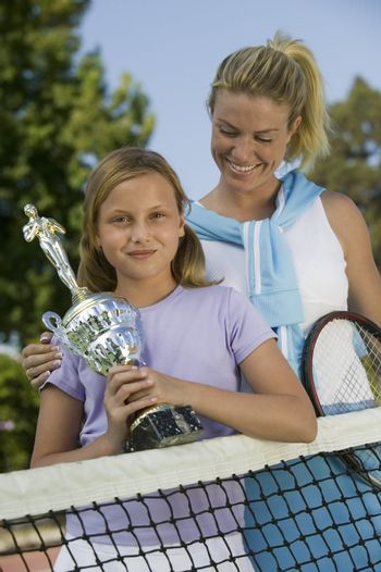 Mother and Daughter at Tennis Net with Trophy