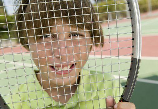 Boy Looking Through Tennis Racket