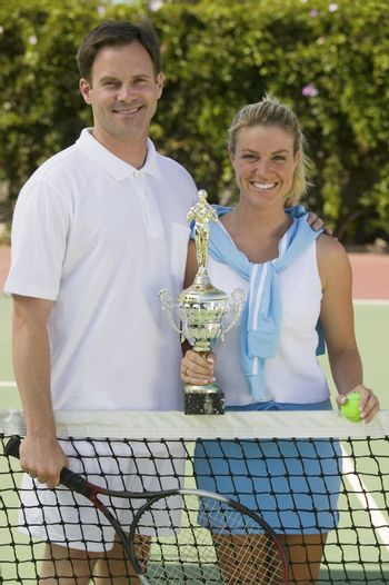 Couple at Tennis Net with Trophy