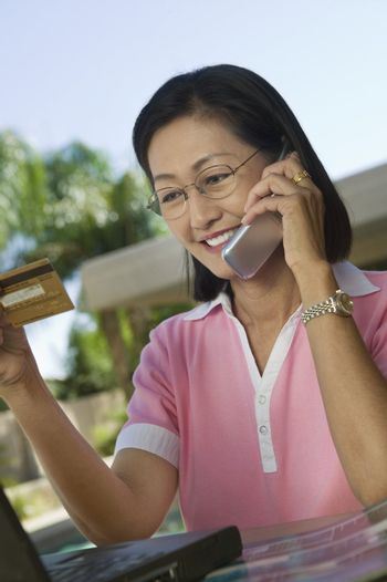 Woman Using Credit Card and Cell Phone for Online Purchase