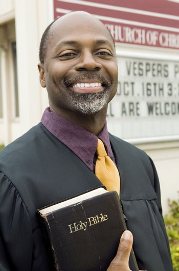 Smiling Preacher in Front of Church