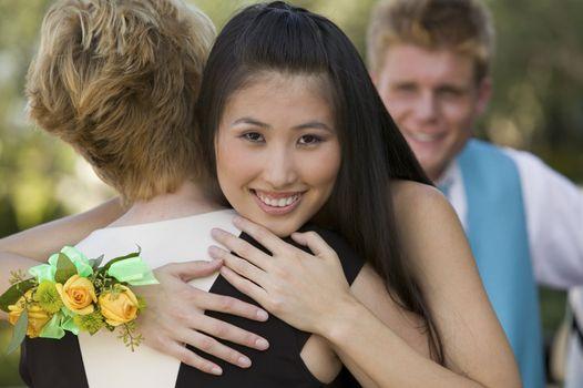 Teenage Girl Hugging Friend at Dance