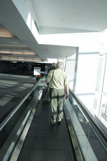 Man in airport on mechanical walkway