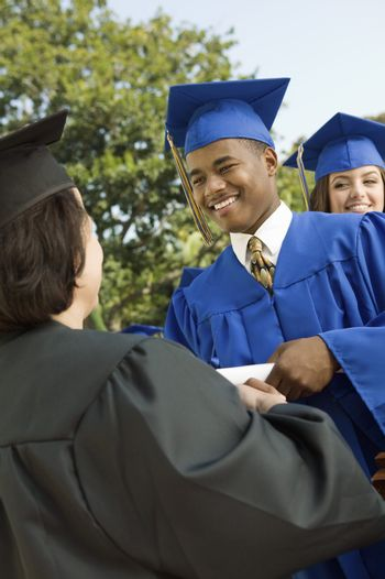 Graduate Shaking Hands and Receiving Diploma