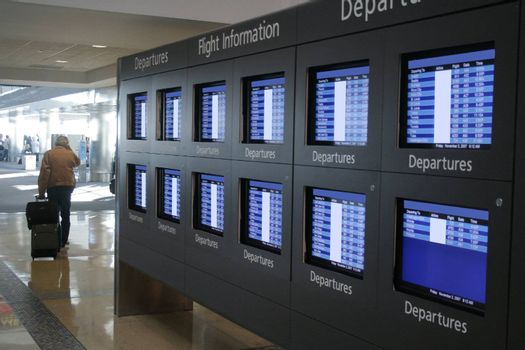 Man in airport walking by screens