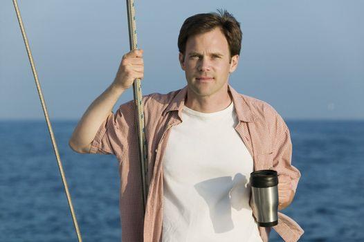 Man with Coffee Mug on Sailboat