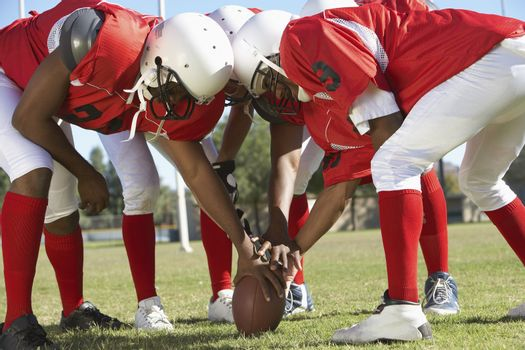 Football Players in Huddle Holding Football