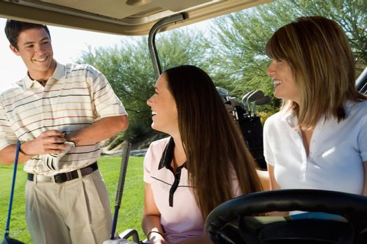 Golfers in Cart Talking on Fairway