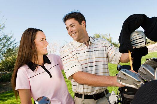 Golfing Couple Grabbing Clubs