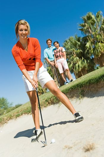 Golfer Standing in Sand Trap While Friends Watch