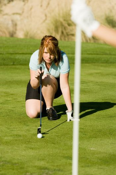 Golfer Lining Up Putt on Putting Green