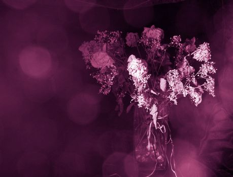 Dried bouquet of faded flowers under somber light speaks of romance gone astray.