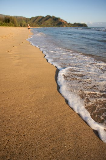 Beach Shoreline in the Early Morning Sun with Jogger